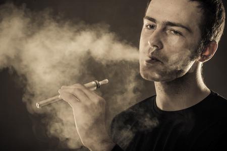 27608050 - man smokes electronic cigarette on dark background