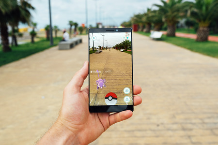 59448930 - batumi, georgia- july 14, 2016: hand holding a smartphone to play the game of augmented reality pokemon go