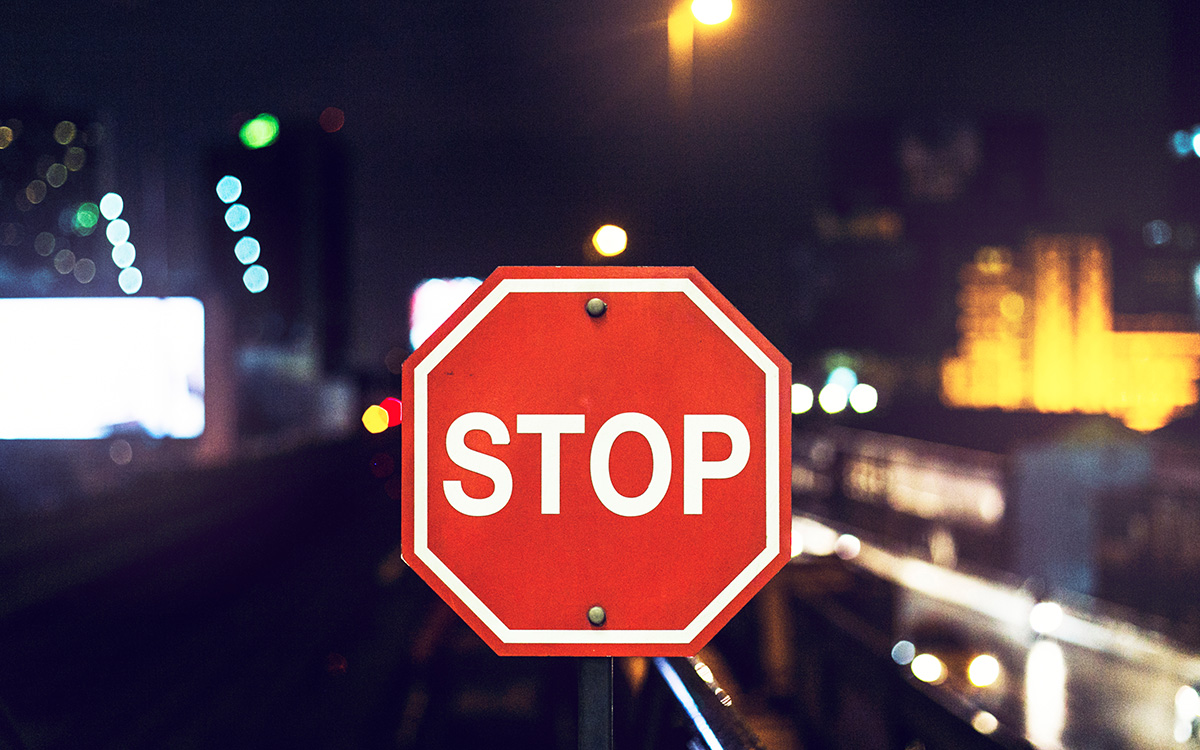 stop sign in front of city lights