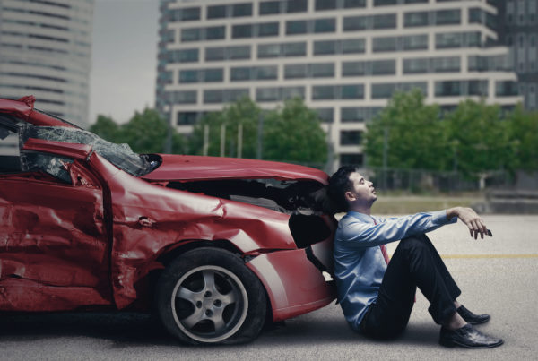 man sitting in front of car that is damaged from auto accident