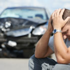 Man sitting in front of car with his hed resting in his hands after a drunk driving accident