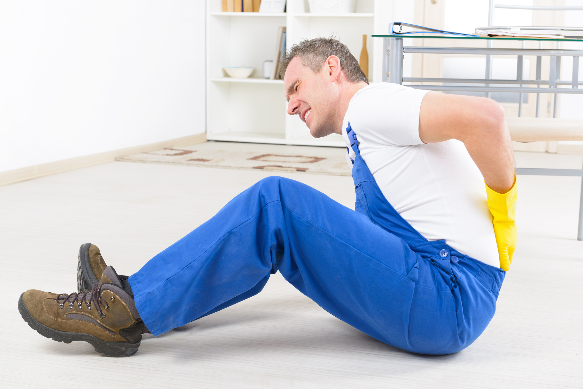 man sitting on the floor in pain holding his back after a fall personal injury lawsuit