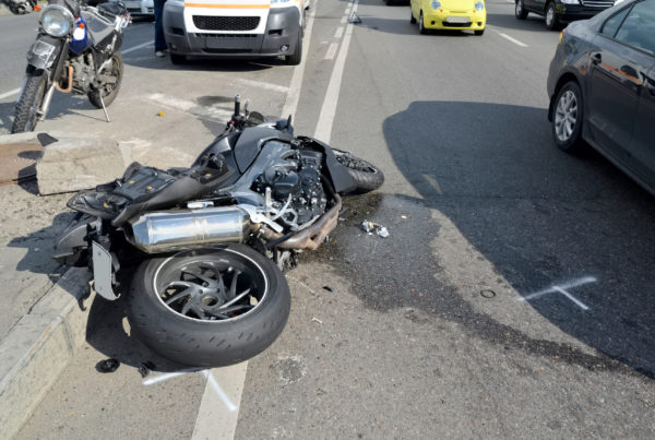 damaged motorcycle laying on ground after motorcycle accident