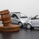 auto accident demonstration with toy cars next to gavel