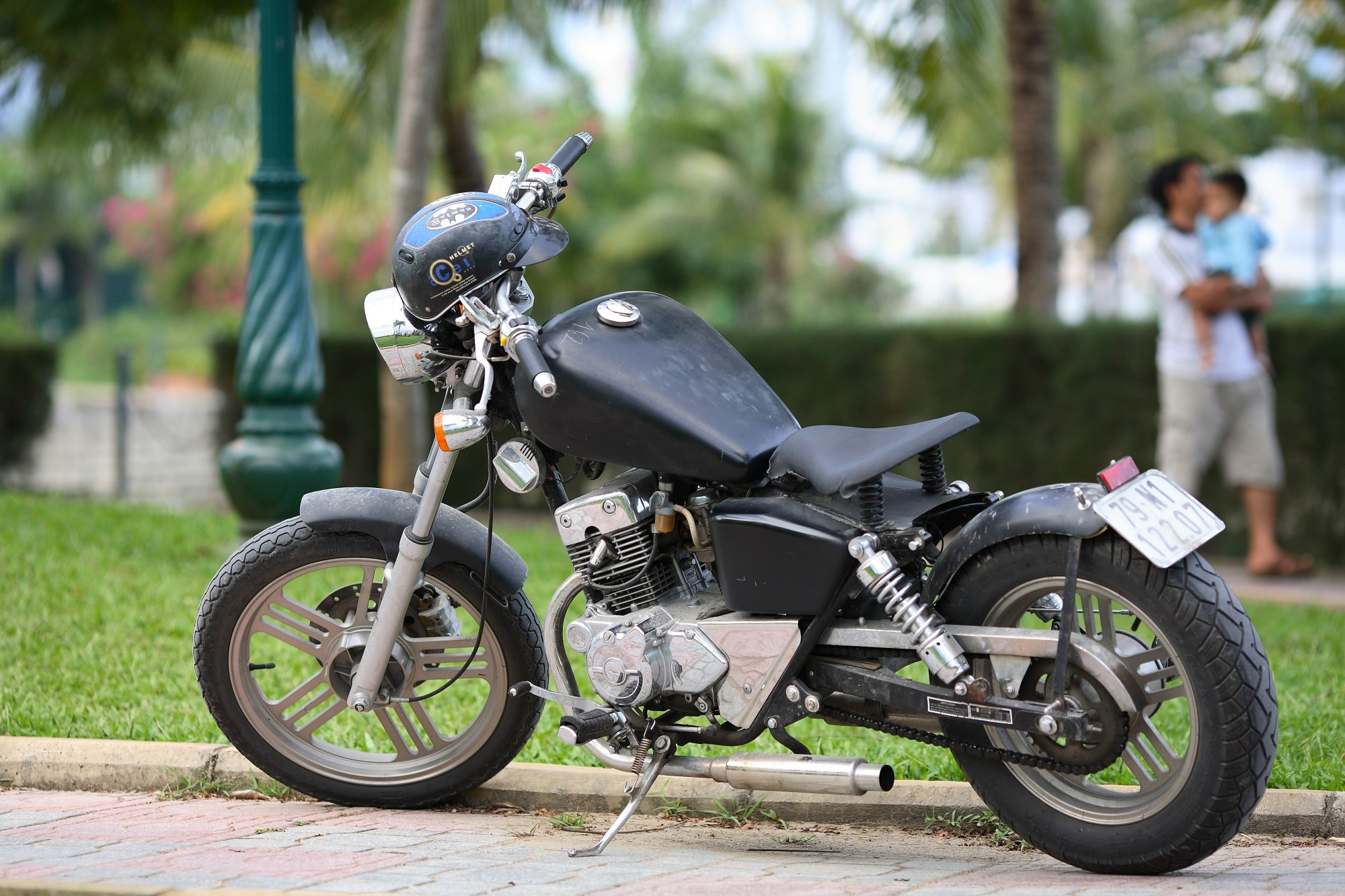 Black motorcycle propped up on kickstand sitting on the curb of the road