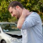 lawyer for whiplash man holding neck after whiplash injury