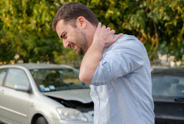 lawyer for whiplash man holding neck after whiplash injury
