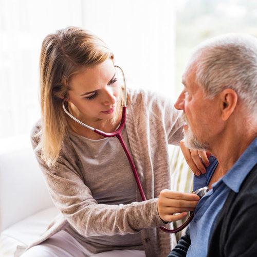nurse caring for senior nusring home resident during coronavirus