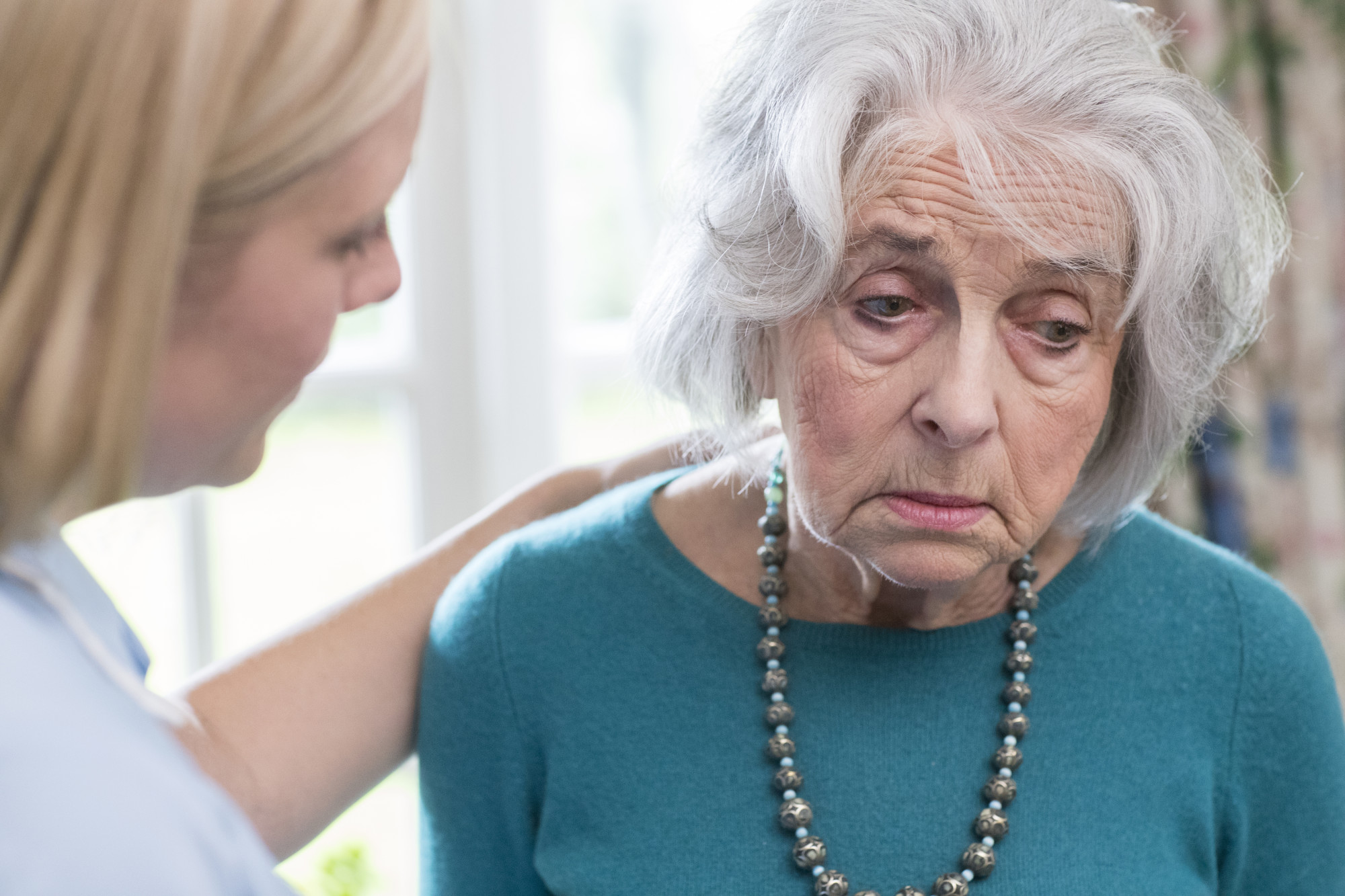 Care Worker Talking To Depressed Senior Woman At Home